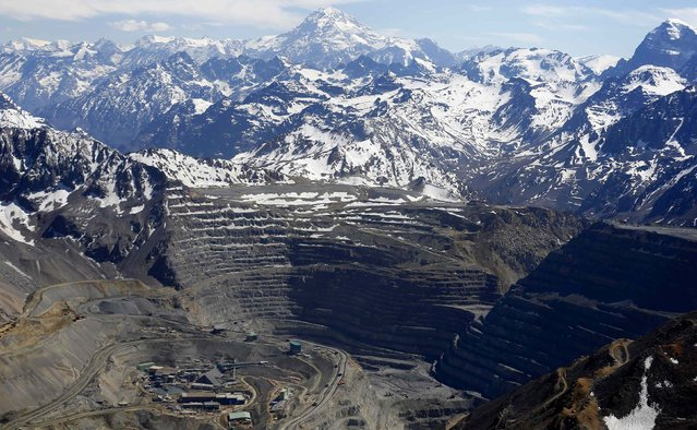 An aerial view of the open pit of Anglo American's Los Bronces copper mine with Aconcagua mount (C) in the background, America's highest peak in the Andes mountain range, and several glaciers, near Santiago city, November 17, 2014. (Photo by Ivan Alvarado/Reuters)