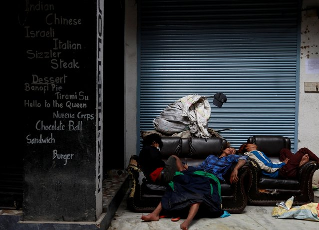 People sleep on an abandoned sofa outside a coffee shop at Thamel, a major tourist hub, after the government implemented restrictions on transport and gatherings and all shops are shuttered for a week as part of safety measures against the spread of the coronavirus disease (COVID-19), in Kathmandu, Nepal on August 25, 2020. (Photo by Navesh Chitrakar/Reuters)
