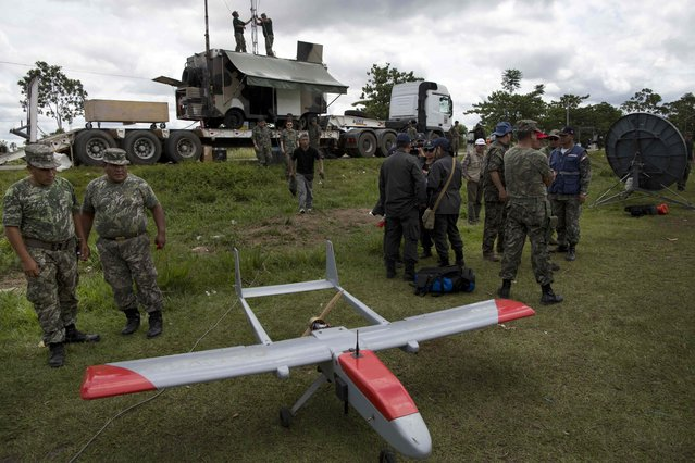 In this November 11, 2014 photo, two soldiers look at a drone, used by the Peruvian Air Force to track illegal mining activity, as they prepare for an operation to eradicate illegal gold mining camps in the area known as La Pampa, in Peru's Madre de Dios region. (Photo by Rodrigo Abd/AP Photo)