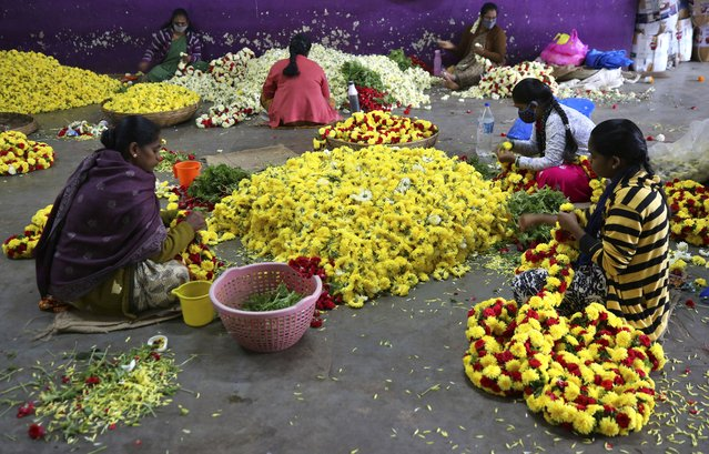 Flower vendors, some wearing face masks as a precaution against coronavirus, prepare garlands at a wholesale market in Bengaluru, India, Thursday, September 24, 2020. (Photo by Aijaz Rahi/AP Photo)