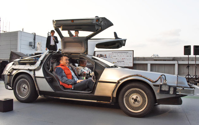 """DeLorean, remodeled similar to the """"Back to the Future Part II"""" time machine, that runs on bioethanol fuel made from old clothes, is driven by retired Japanese professional baseball player Takeshi Yamasaki, right, as retired baseball player Masa Yamamoto smiles during a special celebration event organized by NBC Universal Entertainment Japan to mark the 30th anniversary of the sci-fi film's debut, in Tokyo Wednesday, October 21, 2015. (Photo by Ayaka Aizawa/Kyodo News via AP Photo)"""
