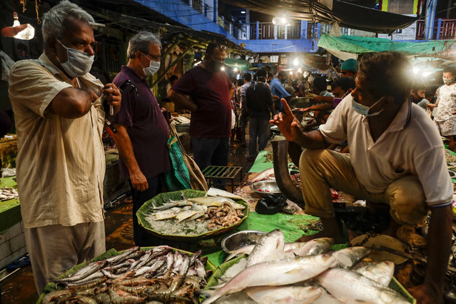 People wear face masks and buy fish at a market in Kolkata, India, Saturday, August 22, 2020. India now has the fourth most fatalities behind the United States, Brazil and Mexico. (Photo by Bikas Das/AP Photo)