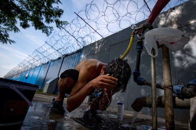A boy washes his hair at a refugee and migrant camp close the border between Serbia and Hungary, near the Serbian town of Horgos, September 29, 2016. (Photo by Andrej Isakovic/AFP Photo)