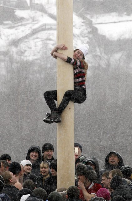 A woman reacts as she climbs up a smooth wooden column to win a contest during the celebrations of Maslenitsa, or Pancake Week, at the Bobrovy Log ski resort on the surburbs of Russia's Siberian city of Krasnoyarsk, March 17, 2013. Maslenitsa is widely viewed as a pagan holiday marking the end of winter and is celebrated with pancake eating, while the Orthodox Church considers it as the week of feasting before Lent. (Photo by Ilya Naymushin/Reuters)