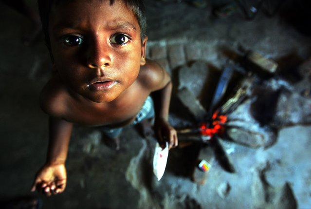 Idusan, 9, a Sri Lankan tsunami survivor, looks at the camera at a shelter for displaced tsunami survivors in Thambiluvil on Sri Lanka's east coast in this January 24, 2005 file photo. (Photo by Arko Datta/Reuters)