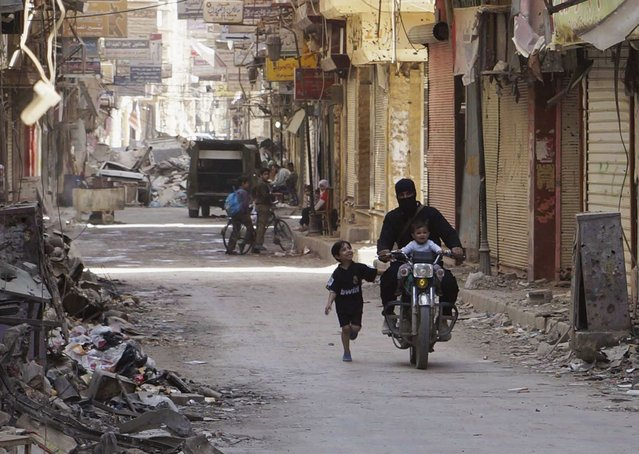 A free Syrian Army fighter rides a motorcycle with a child as a boy runs beside them on a street in Deir al-Zor April  3, 2013. (Photo by Khalil Ashawi/Reuters)