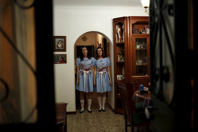 "Sisters dressed as the Grady twins from the movie ""The Shining"" pose for a photo inside their house as they take part in the second edition of ""Noche del Terror"" (Horror night) during Halloween celebrations in the neighborhood of Churriana, near Malaga, southern Spain, October 31, 2015. (Photo by Jon Nazca/Reuters)"