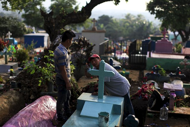 Men paint the grave of a relative during celebration of the Day of the Dead in Nahuizalco, El Salvador November 2, 2015. (Photo by Jose Cabezas/Reuters)