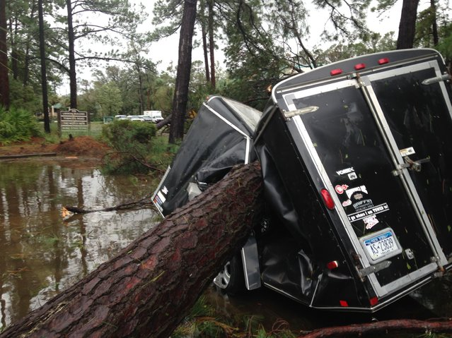 A trailer is destroyed from a fallen tree in the aftermath of Hurricane Matthew at Hilton Head, S.C., on Saturday, October 8, 2016. Matthew plowed north along the Atlantic coast, flooding towns and gouging out roads in its path. (Photo by Jeffrey Collins/AP Photo)