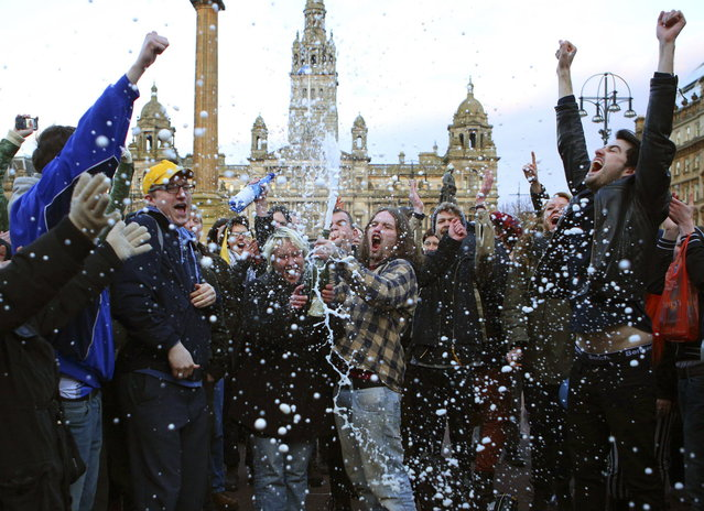 """Revellers spray a bottle of champagne as they celebrate the death of former British prime minister Margaret Thatcher, at George Square in Glasgow, Scotland April 8, 2013. Margaret Thatcher, the """"Iron Lady"""" who transformed Britain and inspired conservatives around the world by radically rolling back the state during her 11 years in power, died on Monday following a stroke. She was 87. (Photo by David Moir/Reuters)"""