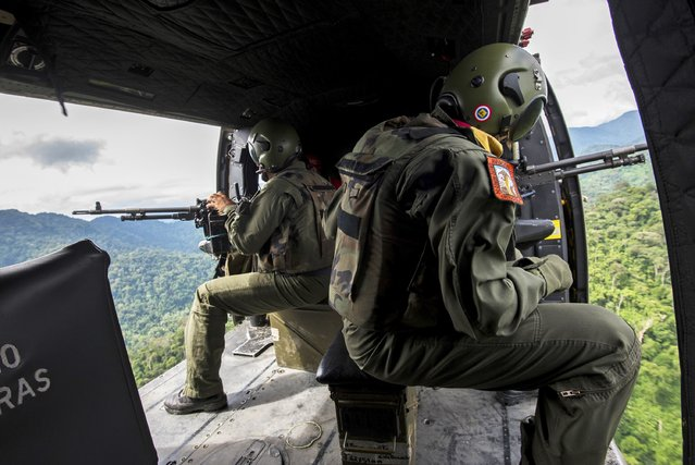 Venezuelan soldiers look out of a helicopter as they patrol during a military operation to destroy clandestine drug laboratories, near the border with Colombia, in the state of Zulia December 6, 2014. Perched on the northeast shoulder of South America with vast expanses of thinly-populated territory and a long Caribbean coast just a three-hour flight from Miami, Venezuela has many geographical advantages for traffickers. (Photo by Manaure Quintero/Reuters)
