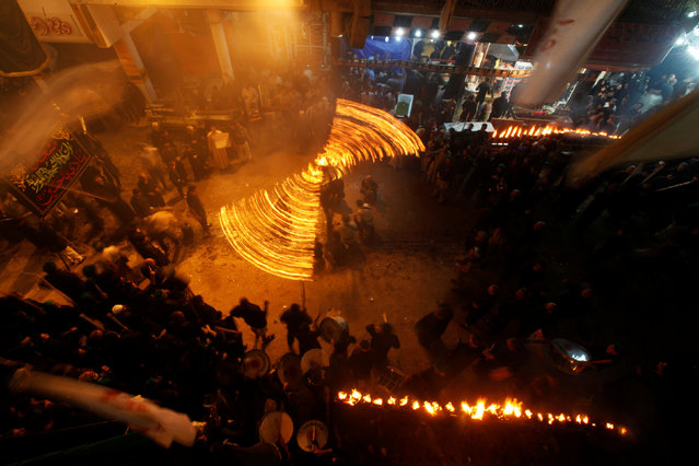 Shi'ite Muslims perform with fire during commemorations for Ashoura in Najaf, October 9, 2016. (Photo by Alaa Al-Marjani/Reuters)