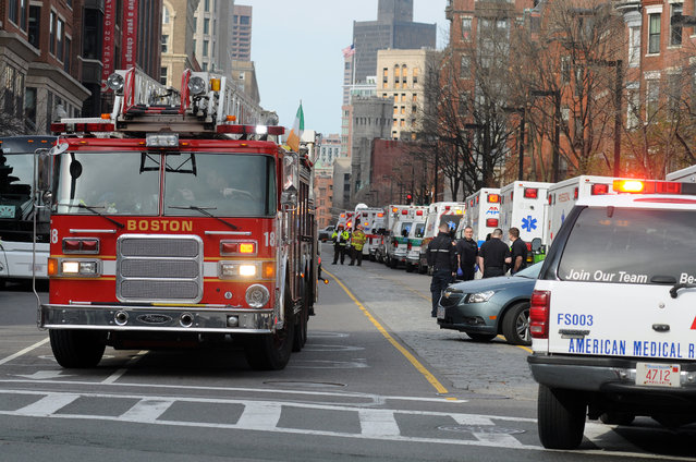 A long line of ambulances wait in a staging area after explosions rocked the finish area of the Boston Marathon on April 15, 2013 in Boston, Massachusetts.  At least two people were killed and 22 wounded when two explosions struck near the finish line of the Boston Marathon, sparking scenes of panic, police said. The streets were littered with debris and blood and paramedics raced off with stretchers as police locked down the area, witness said. TV footage showed an explosion sending up a white plume of smoke along the sidelines of the race. (Photo by John Mottern/AFP Photo)