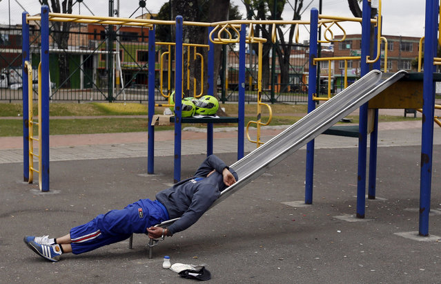 In this September 11, 2014 file photo, a detainee rests, handcuffed to a slide, at a children's playground in a public park in Bogota, Colombia. Authorities have been holding some crime suspects in a public park in western Bogota's La Granja neighborhood because they say there is no more room at a local detention center. (Photo by Fernando Vergara/AP Photo)