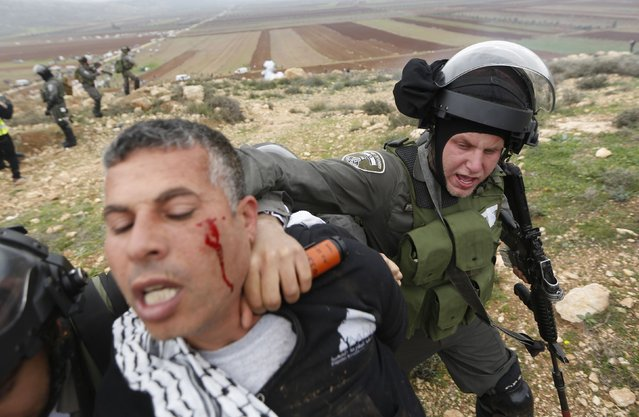 An Israeli border policeman detains a Palestinian protester during clashes following a demonstration against Israeli settlements in the West Bank village of Turmus Aya, near Ramallah  December 19, 2014. (Photo by Mohamad Torokman/Reuters)