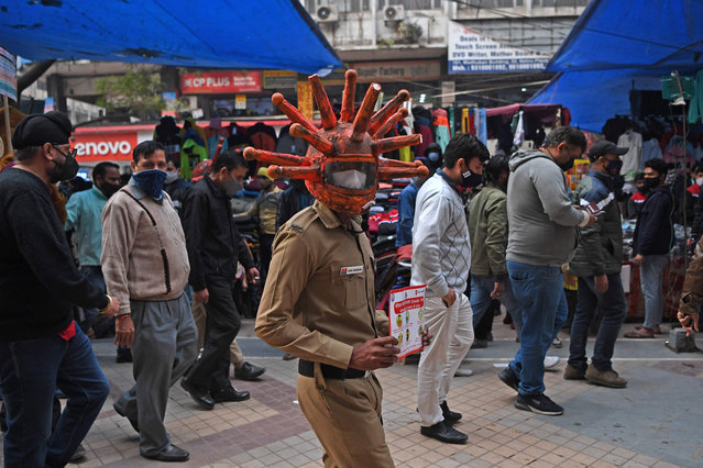 A civil defence volunteer wearing a Covid-19 coronavirus-themed helmet holds a placard as he takes part in an awareness campaign at a market in New Delhi on November 25, 2020. (Photo by Sajjad Hussain/AFP Photo)