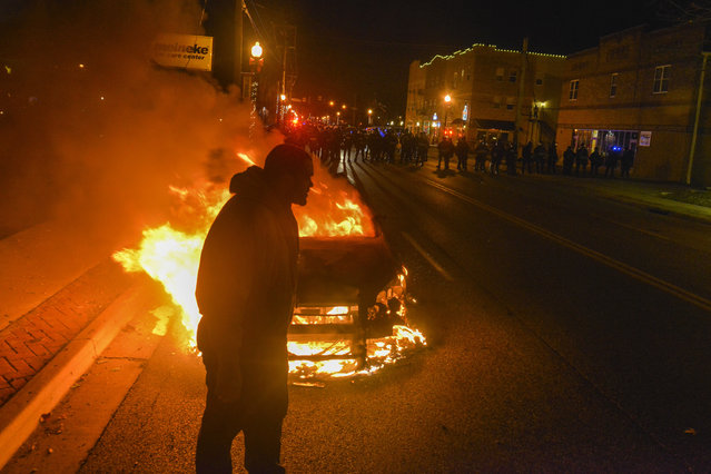 A man stands by a burning St. Louis police car as police in riot gear prepare to clear the streets of people after an announcement that Ferguson police officer Darren Wilson will not be indicted in the fatal shooting of unarmed teenager Michael Brown day, November 24, 2014, in Ferguson, MO. The shooting of Michael Brown, an unarmed black 18-year-old by white Ferguson police officer Darren Wilson, has captivated the nation as a grand jury deliberated to decide whether to charge the officer with a crime. (Photo by Jahi Chikwendiu/The Washington Post)