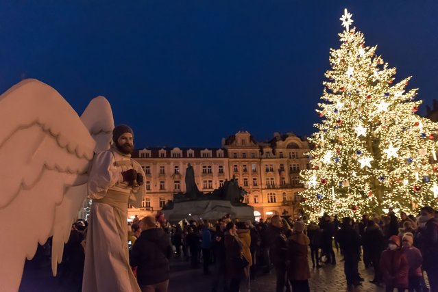 A man wearing an angel costume walks with an illuminated Christmas tree in the background on Old town square in the Czech capital Prague on December 13, 2020 during the third Advent weekend. The famous Christmas market was canceled due to the Corona virus pandemic and current restrictions in the Czech Republic. (Photo by Tomas Tkacik/SOPA Images/LightRocket via Getty Images)