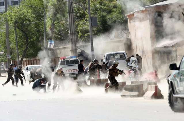 Security forces run from the site of a suicide attack after the second bombing in Kabul, Afghanistan, Monday, April 30, 2018. A coordinated double suicide bombing hit central Kabul on Monday morning, (Photo by Massoud Hossaini/AP Photo)