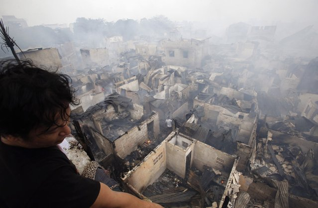 A man looks out from a veranda overlooking houses destroyed by a fire at a slum colony in Quezon city, Metro Manila January 1, 2015. (Photo by Erik De Castro/Reuters)
