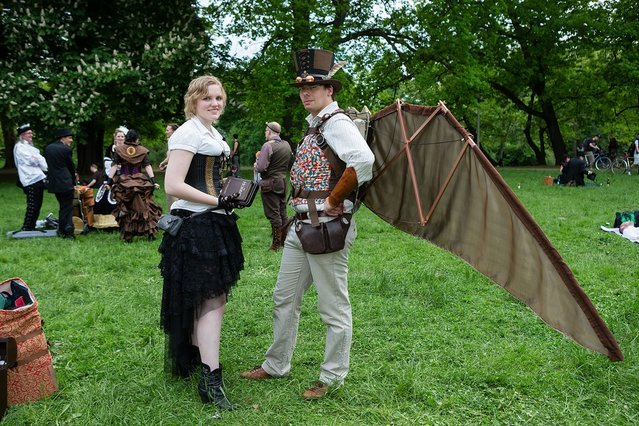 A man in a steam-punk outfit with self-made wings and a woman in Victorian clothing holding the book 'The Hobbit' attend the traditional park picnic on the first day of the annual Wave-Gotik Treffen, or Wave and Goth Festival, on May 17, 2013 in Leipzig, Germany. The four-day festival, in which elaborate fashion is a must, brings together over 20,000 Wave, Goth and steam punk enthusiasts from all over the world for concerts, readings, films, a Middle Ages market and workshops. (Photo by Marco Prosch)