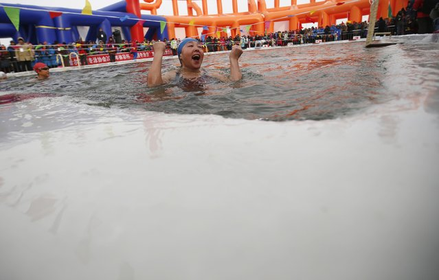 A female swimmer reacts after finishing her competition in a pool carved into thick ice covering the Songhua River during the Harbin Ice Swimming Competition in the northern city of Harbin, Heilongjiang province January 5, 2015. (Photo by Kim Kyung-Hoon/Reuters)
