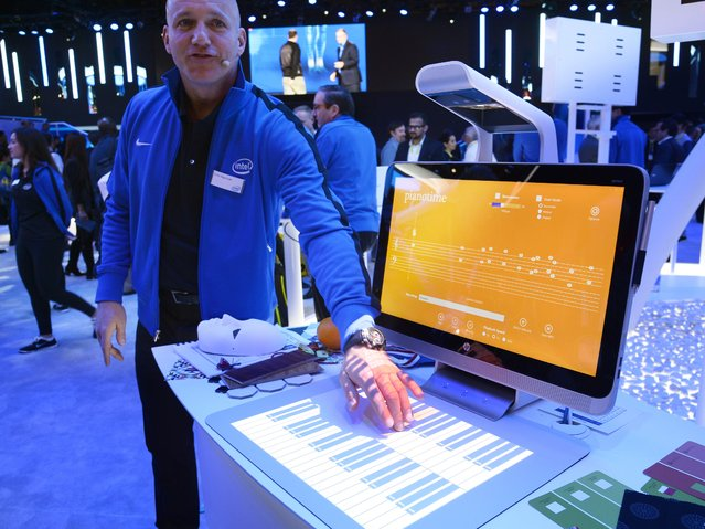 "Colin Daymude plays music via a projected piano keyboard as he demonstrates the HP Sprout, January 6, 2015 at the Intel stand at the Consumer Electronics Show in Las Vegas, Nevada. The  Sprout is a ""blended reality"" PC which combines an all-in-one desktop PC with Intel's RealSense imaging technology, plus a combination scanner and projector, and a touch-sensitive projection surface called a Touchy Mat. (Photo by Robyn Beck/AFP Photo)"