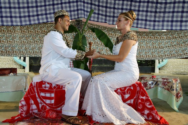 Dutch migrants Reggio de Jong (L) and Elisabeth Cobben hold hands during their wedding ceremony in the second public marriage ever held under the African-American Winti religion in district Para, Suriname, November 18, 2015. (Photo by Ranu Abhelakh/Reuters)