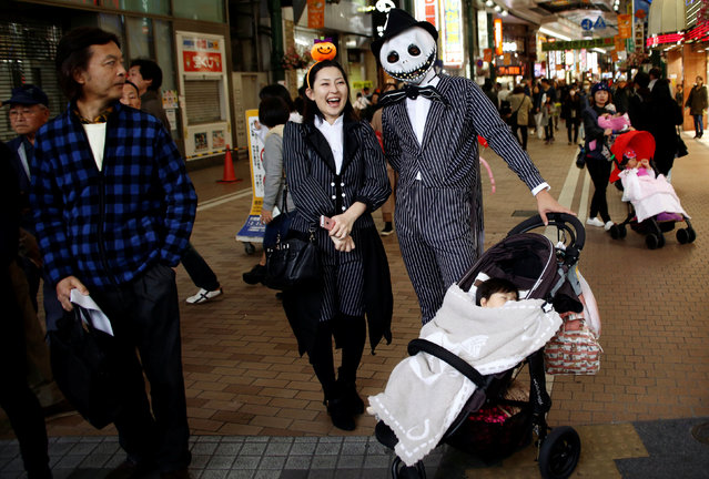 A couple in costumes watch a Halloween parade in Kawasaki, south of Tokyo, Japan October 30, 2016. (Photo by Kim Kyung-Hoon/Reuters)