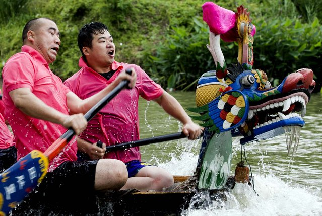 Residents take part in a dragon boat race as part of celebrations for the Duanwu festival also known as the Dragon Boat festival in Hangzhou in eastern China's Zhejiang province Wednesday, June 12, 2013.  The festival originated in China and is marked with eating rice dumplings and racing dragon boats. (Photo by AP Photo)