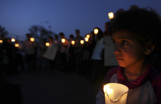 A boy holds a candle during a candlelight vigil to condemn a suicide attack that killed over 100 soldiers in Sanaa May 28, 2012. (Photo by Mohamed al-Sayaghi/Reuters)