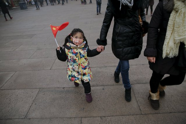 A girl wearing a protective mask waves Chinese flag after visiting the Forbidden City on an extremely polluted day as hazardous, choking smog continues to blanket Beijing, China December 1, 2015. (Photo by Damir Sagolj/Reuters)