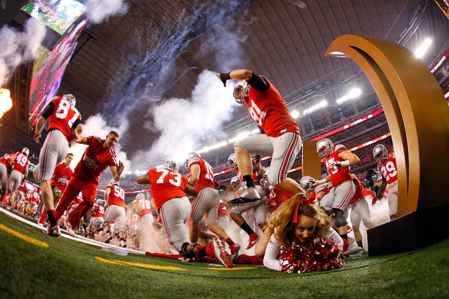 A Ohio State Buckeyes cheerleader falls as the Buckeyes run out to the field before the College Football Playoff National Championship Game at AT&T Stadium on January 12, 2015 in Arlington, Texas. (Photo by Tom Pennington/Getty Images)