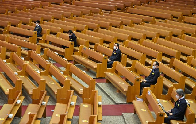Pastors wearing face masks sit among empty benches during an online Christmas service at the Yoido Full Gospel Church in Seoul on December 25, 2020 amid precautions due to the Covid-19 coronavirus. (Photo by Jung Yeon-je/AFP Photo)