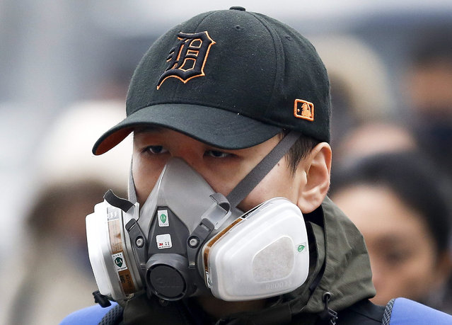 In this December 8, 2015 photo, a man wears a mask to protect himself from pollutants on a heavily polluted day in Beijing. (Photo by Andy Wong/AP Photo)