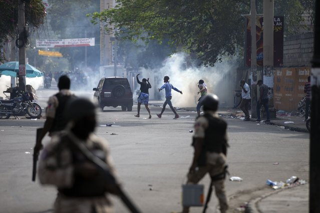 People walk across the street after the police fired tear gas during a nationwide strike demanding the resignation of Haitian President Jovenel Moise in Port-au-Prince, Haiti, Tuesday, February 2, 2021. (Photo by Dieu Nalio Chery/AP Photo)