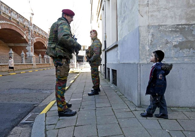 Belgian paratroopers guard outside a Jewish school in the central city of Antwerp January 17, 2015. Security was tight at public buildings and Jewish districts in Brussels and Antwerp and the army provided 150 troops to bolster police presence, following a raid in an apartment in the city of Verviers. (Photo by Yves Herman/Reuters)