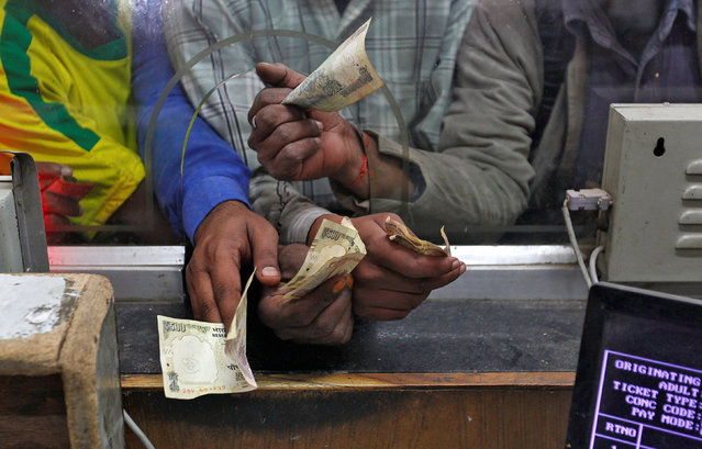 Passengers hold 500 (bottom) rupee banknotes to buy train tickets at a railway booking counter in Allahabad, India, November 9, 2016. (Photo by Jitendra Prakash/Reuters)