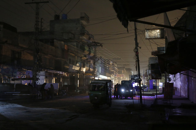 People and auto rickshaws are silhouetted on vehicles headlights on a dark street during widespread power outages in Rawalpindi, Pakistan, Sunday, January 10, 2021. Pakistan's national power grid experienced a major breakdown late night on Saturday, leaving millions of people in darkness, local media reported. (Photo by Anjum Naveed/AP Photo)