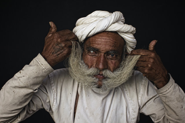 """A big moustache"". Rabari elder showing off his big moustache, the bigger the moustache the more status. Rabari men wear red turbans and white clothes. Sometimes they might use white turbans also. They wear silver bracelets and golden earrings The men like smoking tobacco in Chillums (small Pipe). They also sit together and drink Opium mixed with water, during festivals and ceremonies, after offering it to Gods. Custom is to offer it to each other as well. Location: Image taken close to Mt. Abu, South Rajahstan, India. (Photo and caption by Ingetje Tadros/National Geographic Traveler Photo Contest)"