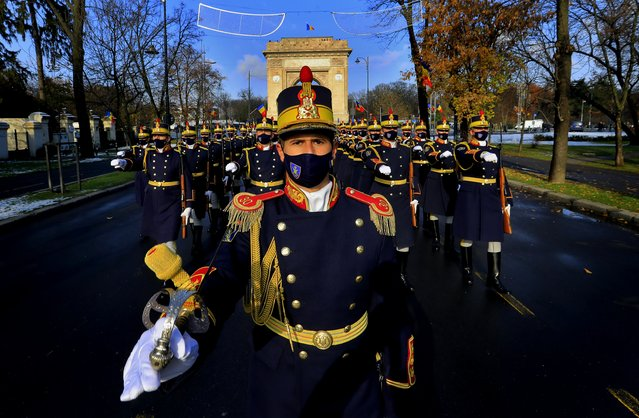 Soldiers of to the Romanian Presidential Honor Guard wearing protection masks march in front of the Triumph Arch during a small ceremony organized to mark Romania's Great Union Day, in Bucharest, Romania, 01 December 2020. Due to the COVID-19 pandemic safety reasons, the event that was marked in recent years with a big military parade, was restricted to a small ceremony without public. Romania is celebrating Great Union Day which commemorates the unification of the three historical provinces of Transylvania, Basarabia and Bucovina with Romania in 1918. (Photo by Robert Ghement/EPA/EFE)
