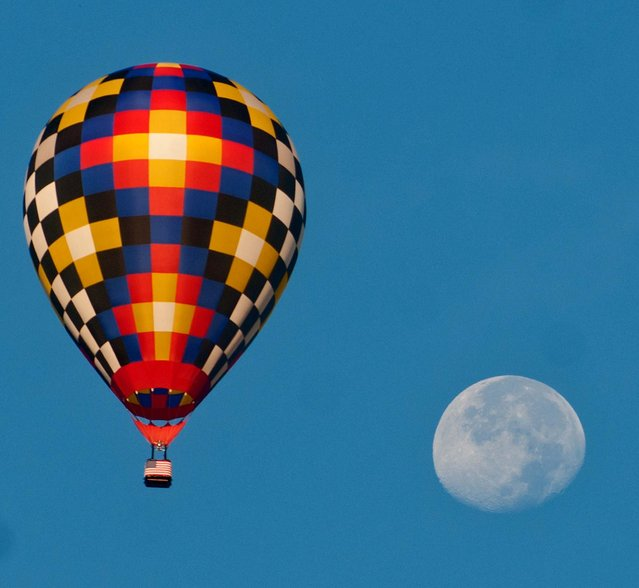A hot air balloon flies with the moon as a backdrop during the first competing flight of the U.S. National Hot Air Balloon Championship, Thursday, July 25, 2013, in Longview, Texas. (Photo by Kevin Green/AP Photo/Longview News-Journal)