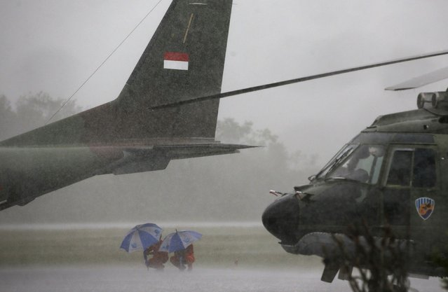 Indonesian Air Force crew members taking part in the search for AirAsia QZ8501 wait out a rain storm under the tail of a cargo plane at the airbase in Pangkalan Bun, Central Kalimantan January 4, 2015. (Photo by Darren Whiteside/Reuters)