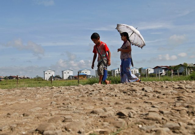 A Rakhine ethnic woman and a boy walk under the sun at the Rakhine ethnic Internally Displaced Persons (IDPs) camp in Sat Yoe Kya quarter, Sittwe, Rakhine State, western Myanmar, 25 August 2016. According to a press release from the office of Myanmar State Counsellor Aung San Suu Kyi, the Myanmar government set up a committee lead by former UN Secretary-General Kofi Annan to find solutions between Rakhine ethnic people and Muslim people in Rakhine State. (Photo by Nyunt Win/EPA)