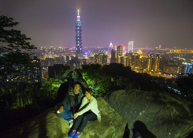 Tourists take a selfie of themselves with the nighttime lights of the city and the landmark Taipei 101 skyscraper as a colorful background as they visit the Elephant hill overlooking Taipei, Taiwan, 20 December 2015. Earlier on 20 December 2015 Taiwan welcomed its 10 millionth visitor, said by officials as a milestones in the tourism sector of Taiwan. (Photo by Ritchie B. Tongo/EPA)