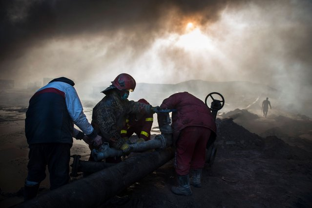 Workers tasked with putting out the fire in an oil well, set ablaze by retreating Islamic State (IS) jihadists, assemble a water pipeline in the town of Qayyarah, some 70 km south of Mosul on November 20, 2016. Firefighters and engineers pumped water into the well in an effort to stop the fire. (Photo by Odd Andersen/AFP Photo)