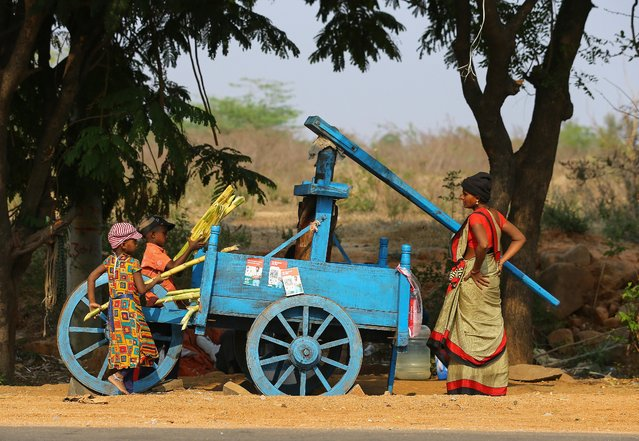 Indian children help a woman to extract juice from sugarcane as she sells them by a roadside on the outskirts of Hyderabad, India, Tuesday, March 16, 2021. (Photo by Mahesh Kumar A./AP Photo)