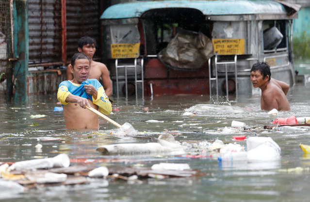 Residents gather plastics and other recyclabble materials along a flooded street caused by monsoon rains and Tropical Storm Son-Tinh in Quezon city, Metro Manila, Philippines on July 17, 2018. (Photo by Erik De Castro/Reuters)