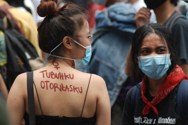 """A slogan that reads """"my body, my authority"""" is seen on an activist's back during a protest marking International Women's Day in Bandung on March 8, 2021. (Photo by Timur Matahari/AFP Photo)"""