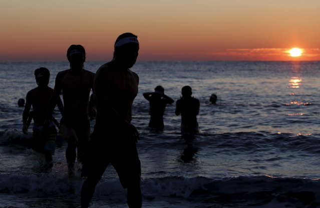 Local swimmers walk out from the ocean after praying to the sun during sunrise to wish for calm waters and good fortune in the new year in Odawara, Kanagawa prefecture, west of Tokyo, Japan, January 1, 2016. (Photo by Yuya Shino/Reuters)